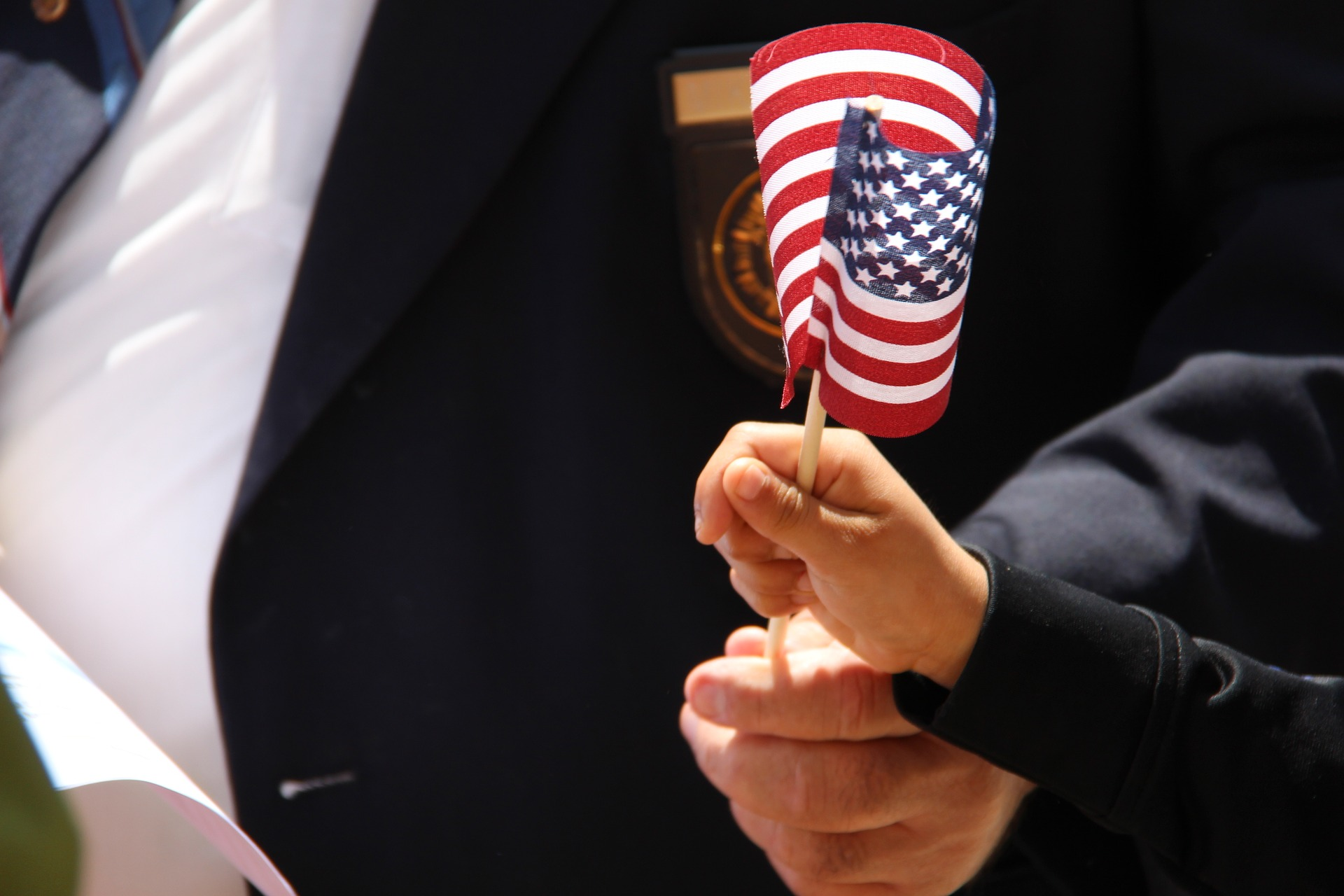 Man and Boy Holding a small stick American Flag