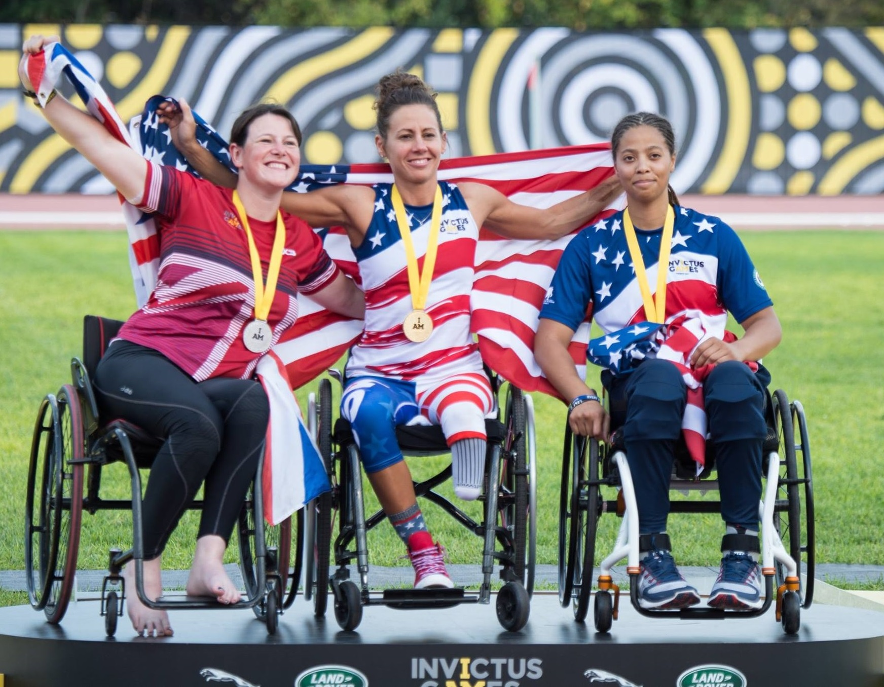 Three American woman on Invictus games podium wearing gold, silver and bronze medals